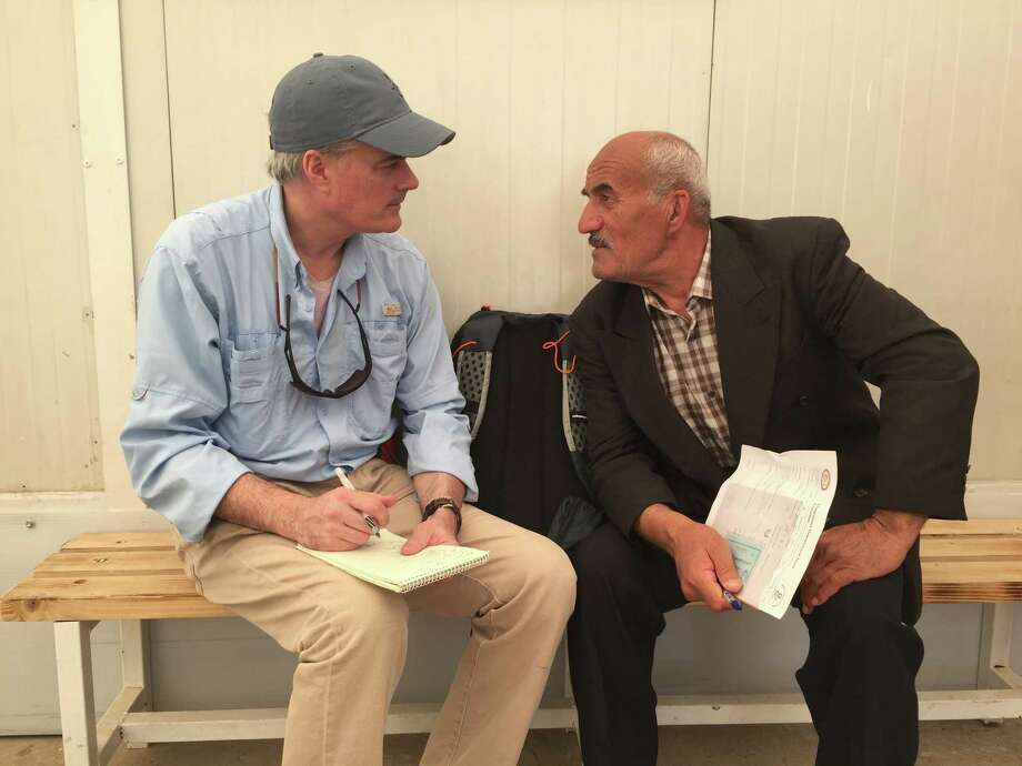 Greenwich journalist Tom Gallagher speaking with a man named Dominic, an internally displaced Iraqi Christian waiting his turn to see a doctor at a health clinic in Erbil, Iraq. Photo: Tom Gallagher /National Catholic Reporter / Greenwich Time Contributed