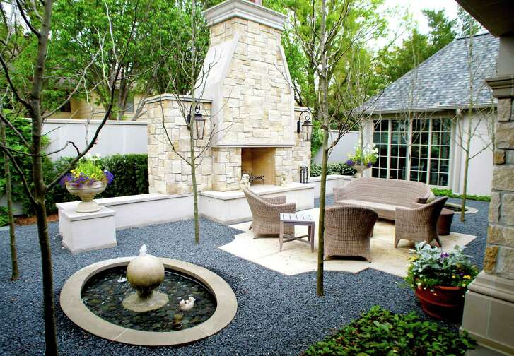 The shape of the patio is inspired by the architecture of this outdoor fireplace and the angle of the home's roof in this French-courtyard-inspired design by landscape architect Lanson B. Jones. The fountain, which provides a second focal point, and soft gravel, instead of grass, are both hot trends right now.