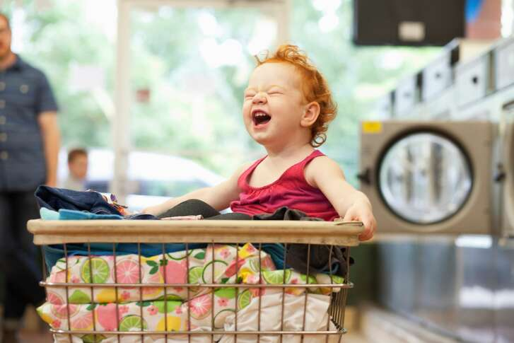 Toddler sitting in laundry basket, laughing