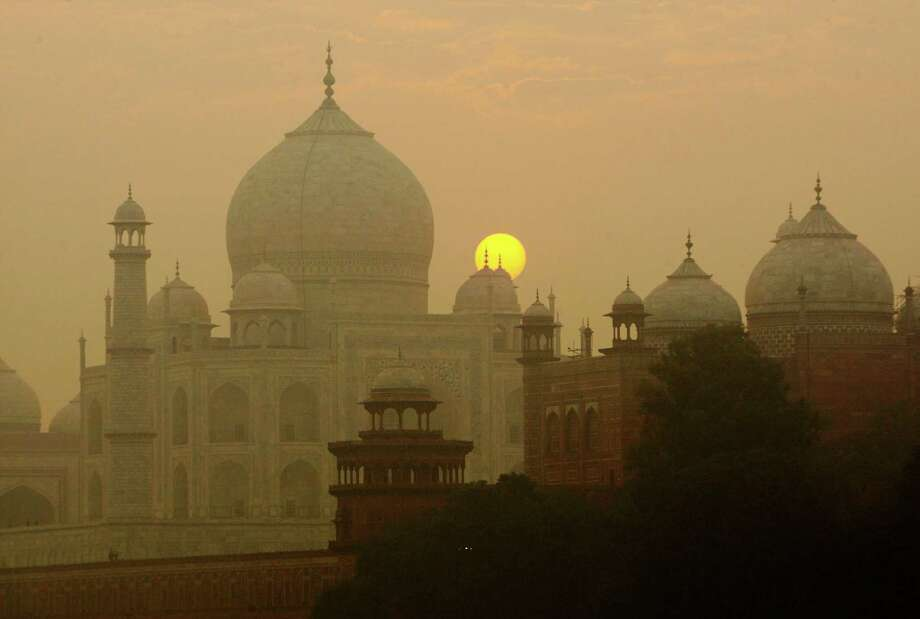 FILE - In this Nov. 18, 2009, file photo, the sun rises over the Taj Mahal in Agra, India. Archaeological experts say insects proliferating from a polluted river near the Taj Mahal are marring the intricate marble inlay work by leaving greenish black patches of waste on the walls of the 17th century monument of love. (AP Photo/Gurinder Osan, File) Photo: Gurinder Osan, STF / Copyright 2016 The Associated Press. All rights reserved. This material may not be published, broadcast, rewritten or redistribu