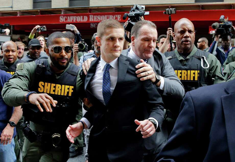 John Nero, center left, and Edward Nero, center right, brother and father of Officer Edward Nero, one of six Baltimore city police officers charged in connection to the death of Freddie Gray, are escorted out of a courthouse after Nero was acquitted of all charges in his trial in Baltimore, Monday, May 23, 2016. (AP Photo/Patrick Semansky) Photo: Patrick Semansky, STF / Copyright 2016 The Associated Press. All rights reserved. This material may not be published, broadcast, rewritten or redistribu