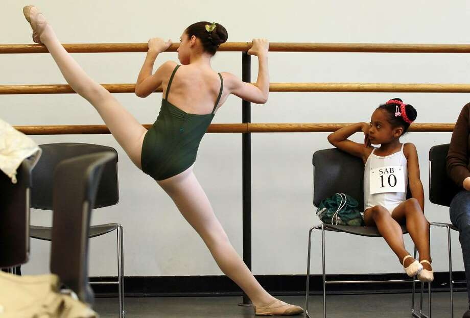 NEW YORK - APRIL 19:  Ashlee Benjamin, 6, waits to audition as her sister Lyllian Rodriguez, 12, stretches before class before audtions for coveted spots at the famed School of American Ballet in the Rose Building at Lincoln Center April 19, 2010 in New York City. Today is the first day in a series of audtions for new students between the ages of 6 and 10. Dancers trained at the school currently perform on the rosters of more than 70 national and international companies.  (Photo by Mario Tama/Getty Images) *** Local Caption *** Lyllian Rodriguez;Ashlee Benjamin Photo: Mario Tama, Getty Images / 2010 Getty Images