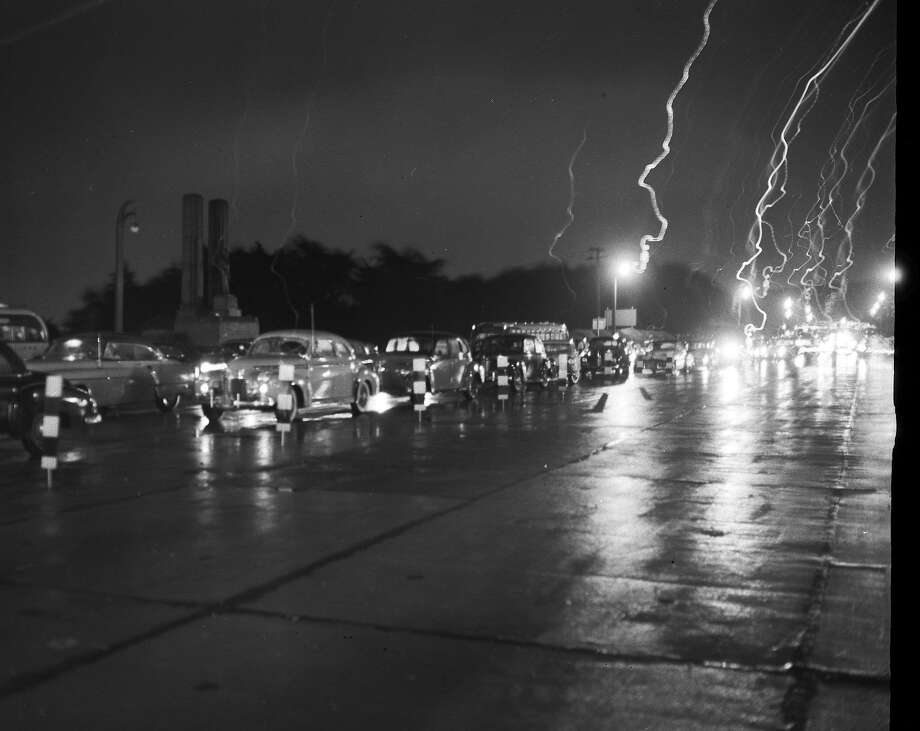 The wind was blowing so hard near the Golden Gate Bridge, Chronicle photographer Bill Young had trouble holding his camera still. He threw flash powder in the air, and the wind made it look like lightning behind the row of cars at the bridge, which was closed for three hours the evening of Dec. 1, 1951. Photo: Bill Young, The Chronicle
