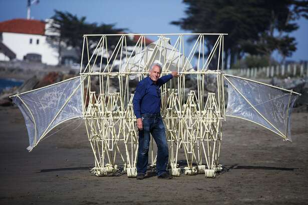 """Dutch artist Theo Jansen strikes a pose for media in front of one of his""""Strandbeest� sculptures, at Crissy Field, in San Francisco, California, on Wednesday, May 18, 2016. His wind-propelled kinetic sculptures will be on view at the Exploratorium."""