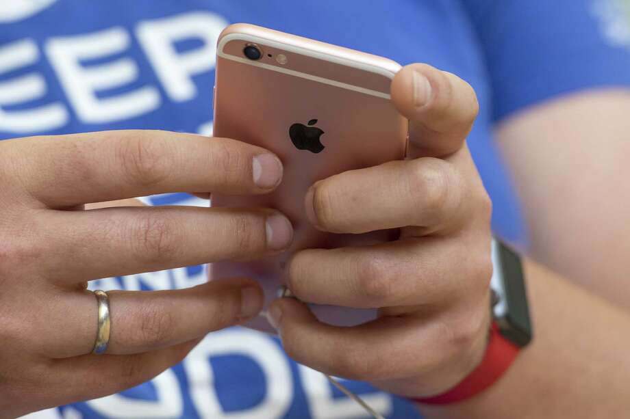 """A shopper views an Apple Inc. iPhone 5SE during the grand opening of the company's new flagship store at Union Square in San Francisco, California, U.S., on Saturday, May 21, 2016. The flagship location boasts 40-foot-tall doors opening onto the square and comprises five departments, or what Apple prefers to call """"features."""" Photographer: David Paul Morris/Bloomberg Photo: David Paul Morris, Bloomberg / © 2016 Bloomberg Finance LP"""
