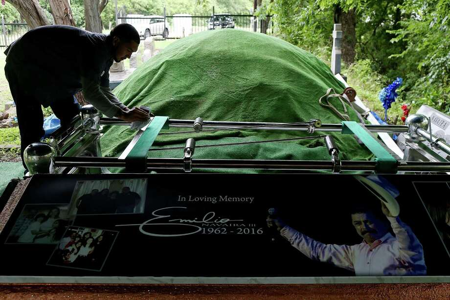 Jeremy Baxa cleans a metal frame at the burial site for Tejano music superstar Emilio Navaira, III, at San Juan Cemetery in Berg's Mill, Monday, May 23, 2016. The funeral mass will be at San Fernando Cathedral. Navaira, 53, died suddenly on May 16 at his home in New Braunfels. Photo: Jerry Lara /San Antonio Express-News / © 2016 San Antonio Express-News