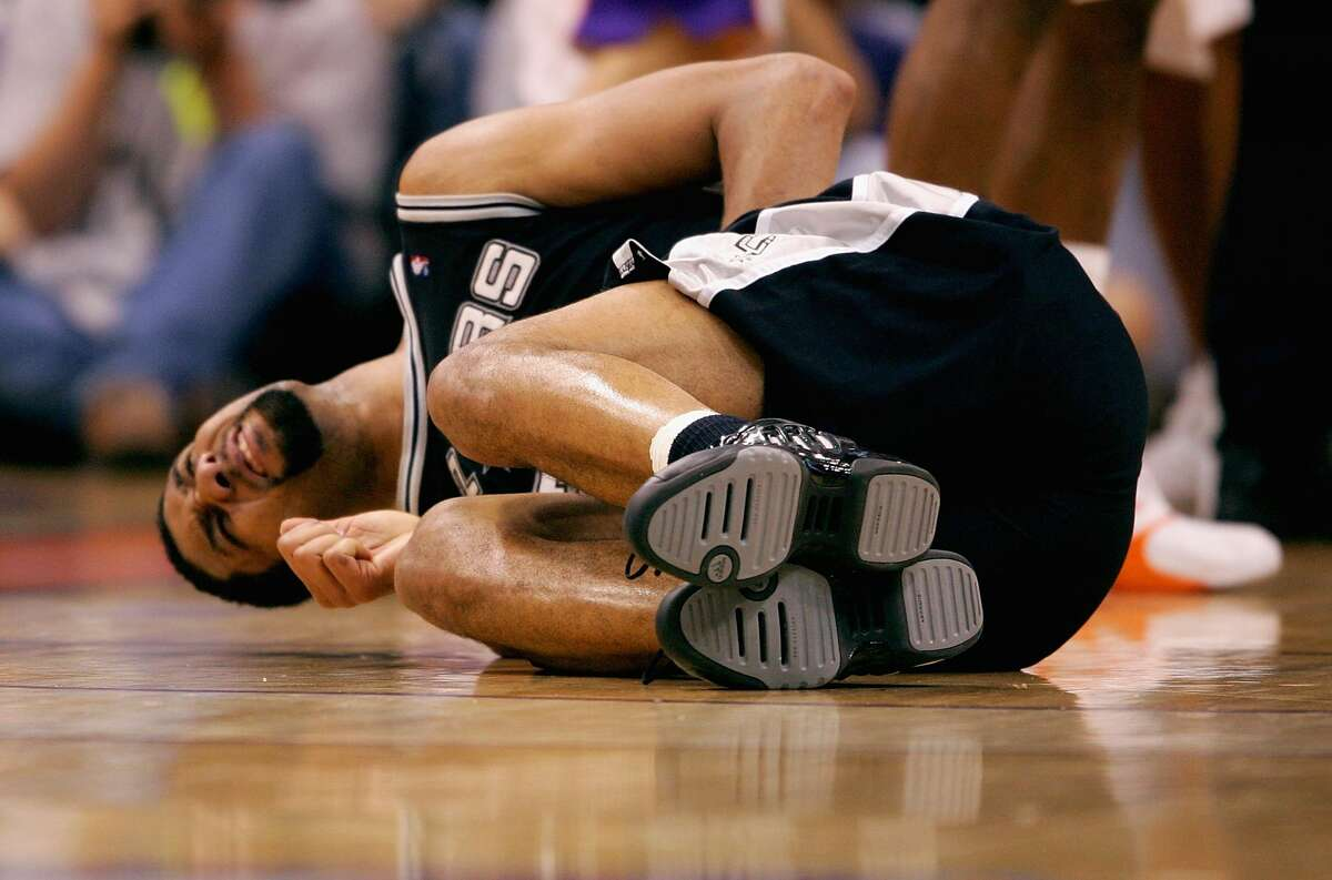 PHOENIX - JUNE 1: Tim Duncan #21 of the San Antonio Spurs lays on the ground after being kicked in the groin in the game against the Phoenix Suns in Game five of the Western Conference Finals during the 2005 NBA Playoffs at America West Arena on June 1, 2005 in Phoenix, Arizona. The Spurs won 101-95 and win the series 4-1 to advance to the NBA Finals. NOTE TO USER: User expressly acknowledges and agrees that, by downloading and/or using this Photograph, user is consenting to the terms and conditions of the Getty Images License Agreement (Photo by Elsa/Getty Images)