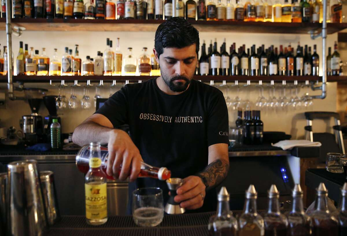 """Bartender Oswaldo Gonzalez demonstrates how to make a Spritz """"cocktail di vino"""" at Ca'Momi restaurant May 17, 2016 in Napa, Calif."""