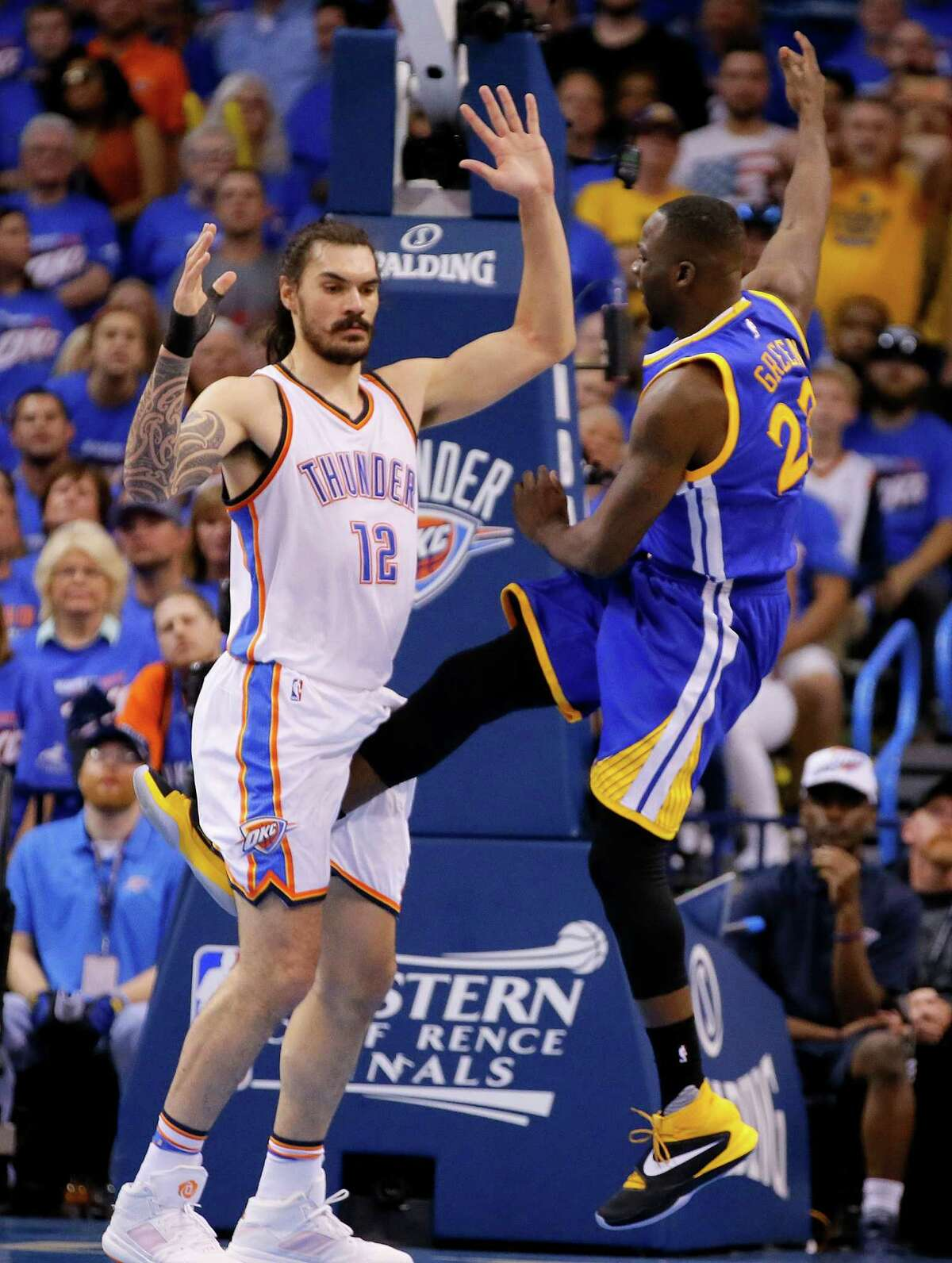 In this Sunday, May 22, 2016 photo, Golden State's Draymond Green's leg is between the legs of Oklahoma City's Steven Adams (12) during Game 3 of the Western Conference finals in Oklahoma City. Draymond Green has been suspended by the NBA for Game 4 of the Western Conference finals for kicking Adams in the groin.