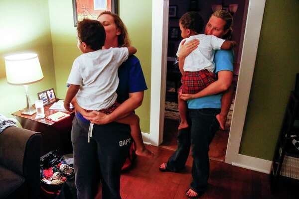 Angela Sugarek, left, and her wife, Carol Jeffery, are reunited with their foster children, ages 3 and 4, as they prepare to spend their first night back together Monday, nearly two months after Child Protective Services removed the children from their home.
