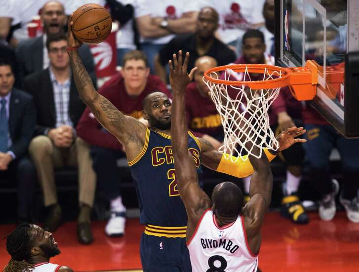 The Cavaliers'  LeBron James winds up to throw one down against Bismack Biyombo, who was a strong inside presence for the Raptors with 14 rebounds and three blocked shots.