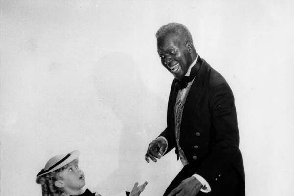"""Shirley Temple and tap dancer Bill """"Bojangles"""" Robinson are shown in a scene from the 1935 motion picture """"The Little Colonel,"""" one of four movies they appeared in together. (AP Photo)"""
