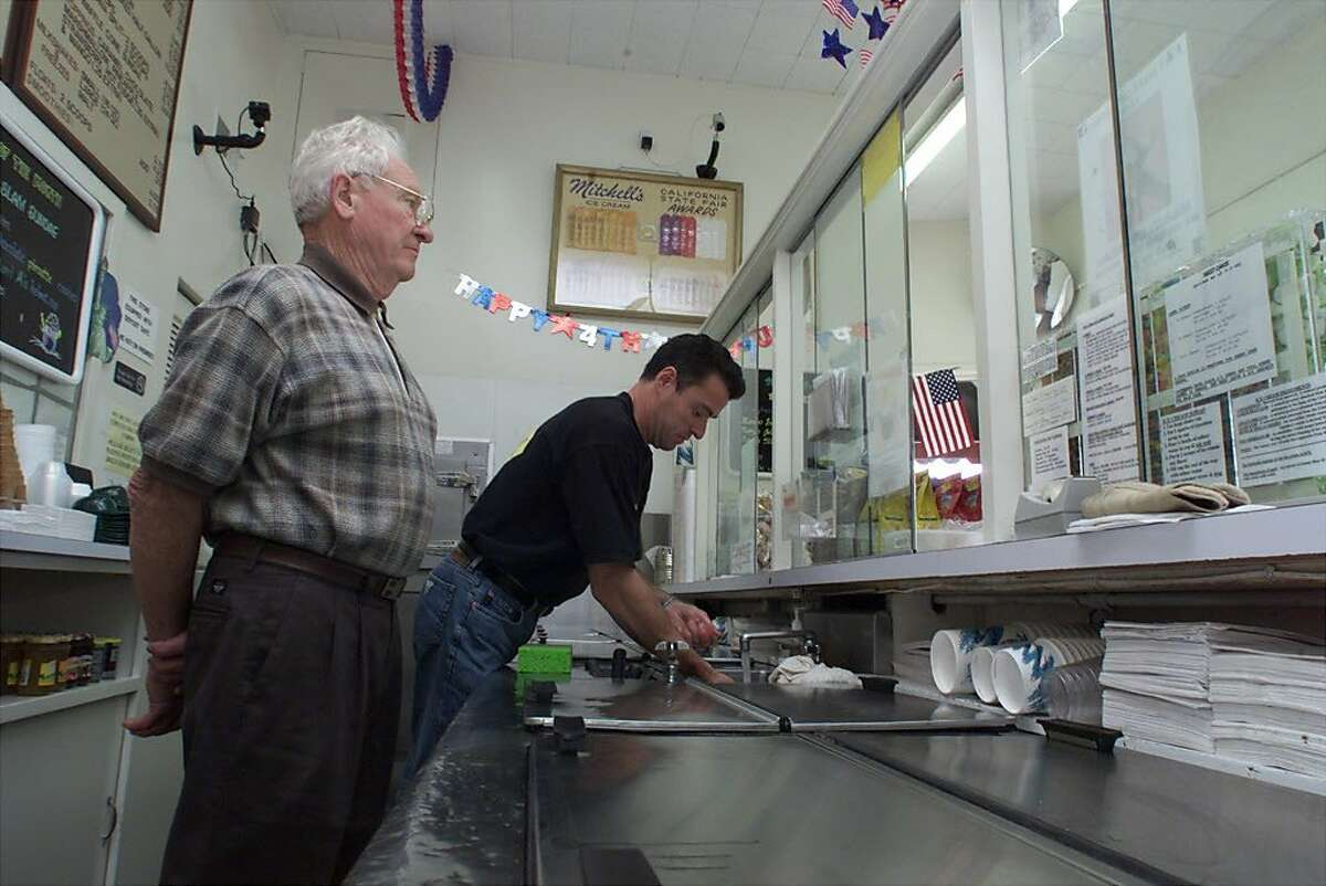 Larry Mitchell owner and founder of Mitchell's Ice Cream Parlor waits for a customer to make up her mind on flavors while his son Brian works the counter the at Mitchell's Ice Cream Parlor on San Jose St in San Francisco.
