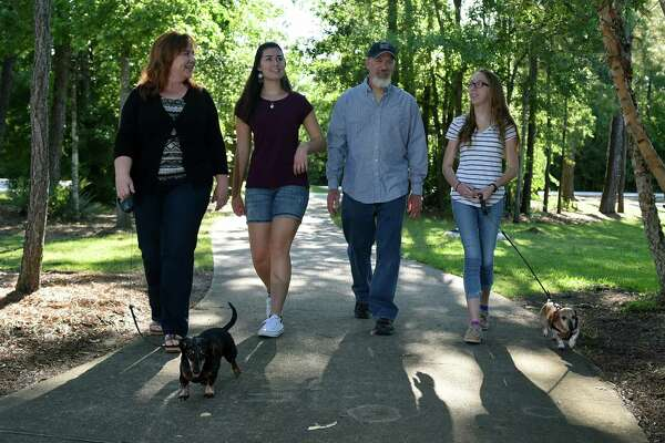 Dina Ohlemeier, left, joins College Park High School junior and foreign exchange student Juli Wiethoff, her husband Lane and their daughter Avery, also a junior at College Park, on a walk near their home in The Woodlands.