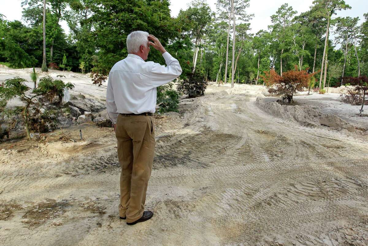 Darrin Duling takes in the damage at the former lawn area of Mercer Botanic Gardens, damaged by the rain and flooding of Cypress Creek in April.