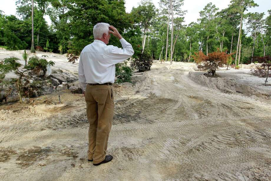 Darrin Duling takes in the damage at the former lawn area of Mercer Botanic Gardens, damaged by the rain and flooding of Cypress Creek in April. Photo: Elizabeth Conley, Staff / © 2016 Houston Chronicle