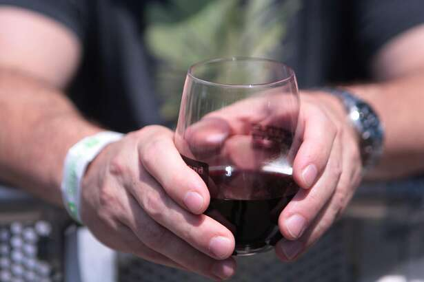 A fan holds a glass of wine as he rests against the barricade at the 2014 Bottlerock Napa Valley music, food and wine festival on Friday, May 30, 2014 in Napa, Calif.