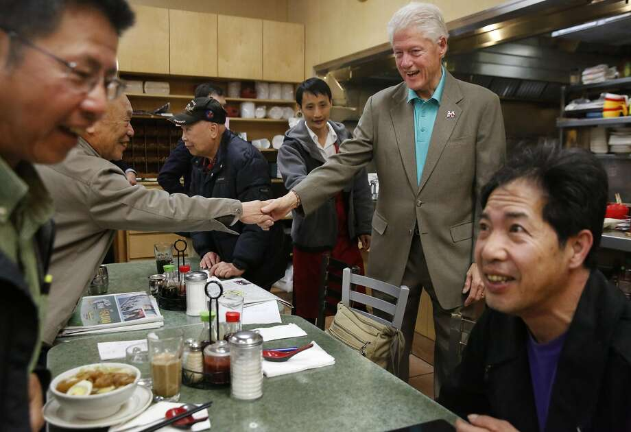 Former President Bill Clinton shakes hands with guests at Washington Bakery and Restaurant in Chinatown. Photo: Leah Millis, The Chronicle
