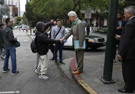 Former President Bill Clinton gets a thumbs down as he shakes hands with pedestrians during a surprise visit in Chinatown May 24, 2016 in San Francisco, Calif.