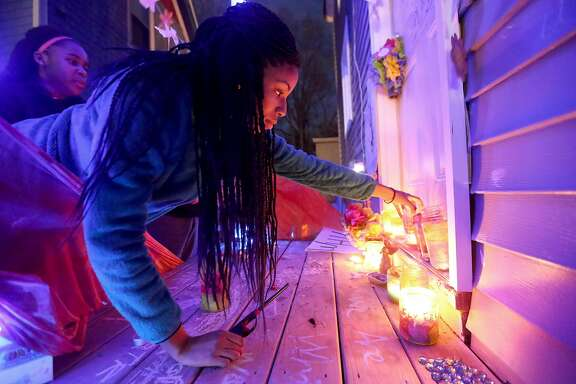 Kaylahn Jones, places a candle on the porch of the Madison, Wis., residence where Tony Robinson was killed during a candlelight vigil marking the one year anniversary of the police shooting death of Robinson on Sunday, March 6, 2016. Community members planned a series of events over the weekend to mark the one-year anniversary of Robinson, who was unarmed when fatally shot by a white police officer on March 6, 2015. They say they hope the events draw attention to the lack of tangible difference in the city's policing. (John Hart/Wisconsin State Journal via AP) MANDATORY CREDIT