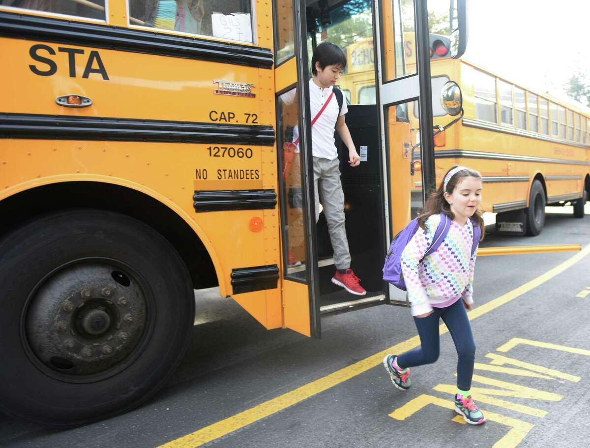 Fifth-grader Koto Freeman, left, and kindergartener Sophia Sinclair get off the school bus at North Street School in March. The debate over start times for elementary, middle and high school students continues.