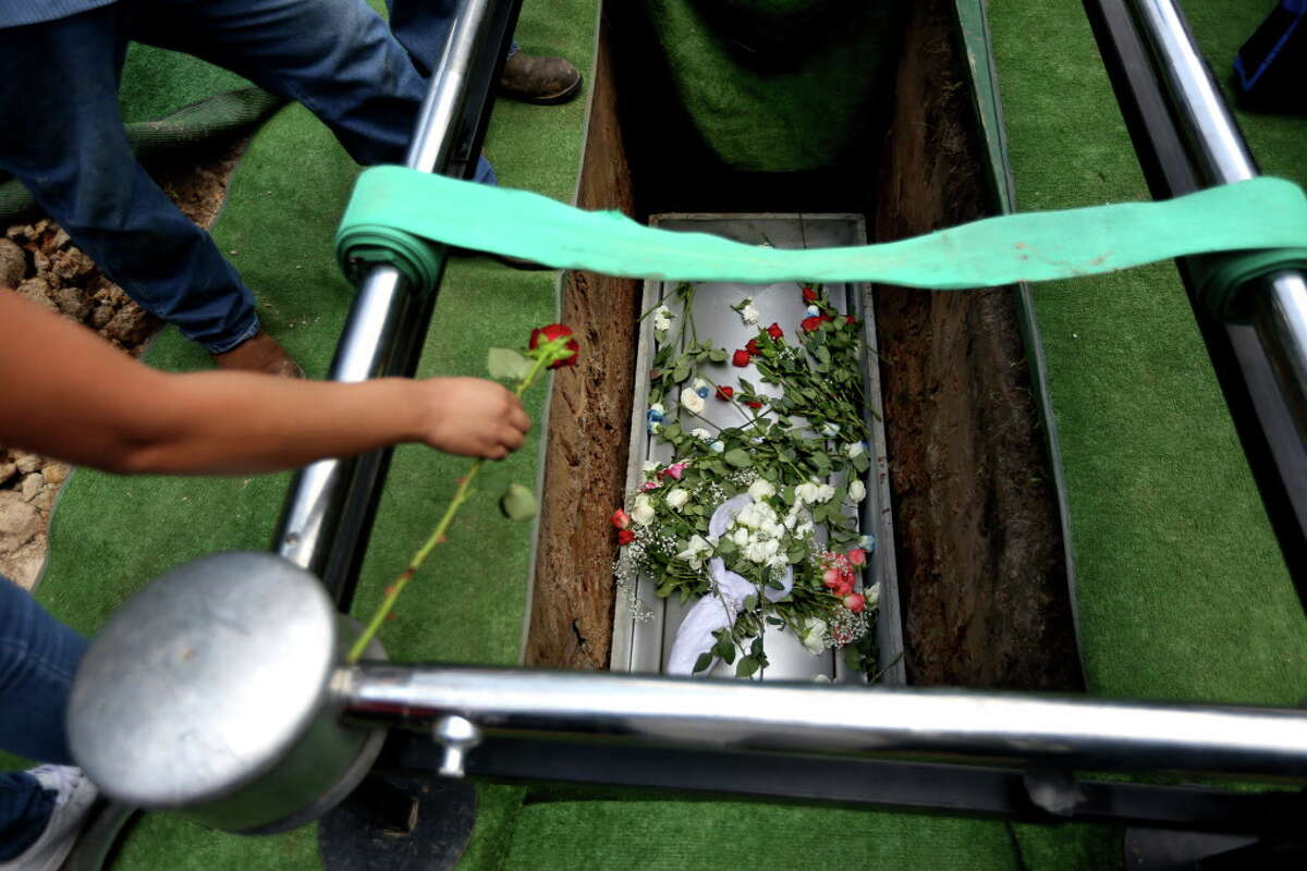Flowers are tossed into the grave Josue Flores, 11-years-old, at the conclusion of a funeral service at Historic Hollywood Cemetery, Tuesday, May 24, 2016, in Houston. Josue was stabbed to death in north Houston as he walked home from school.