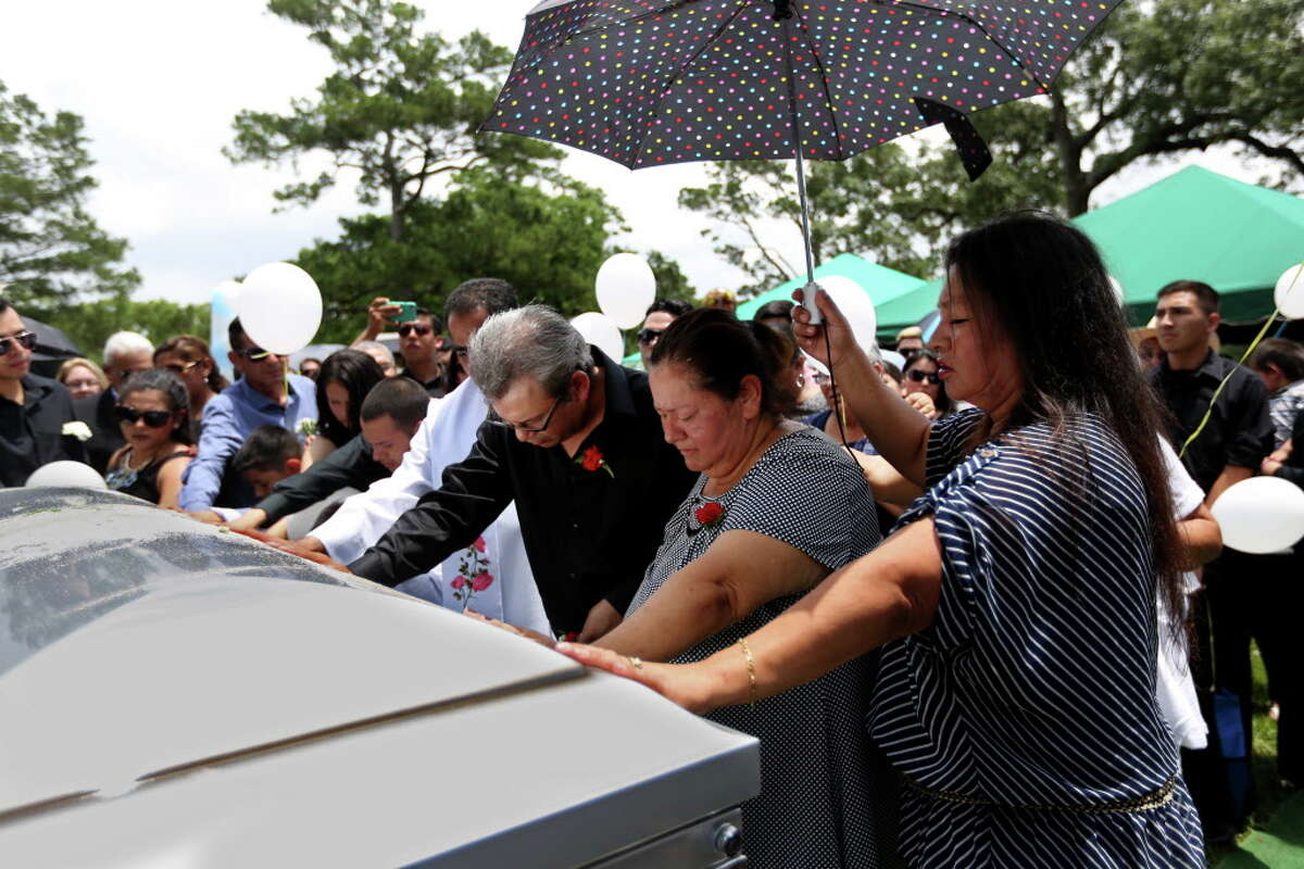 Juan Flores Sr. and his wife, Maria Flores, say a prayer over the casket of their 11-year-old son, Josue Flores, during a funeral service at Historic Hollywood Cemetery, Tuesday, May 24, 2016, in Houston. Josue was stabbed to death May 18 in north Houston as he walked home from school.