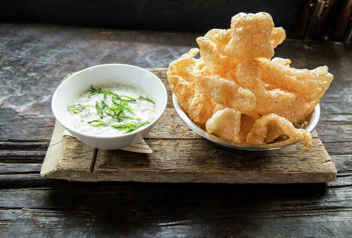 A bowl of hot pork cracklins served with French spring onion dip is among the new bar snacks at the Hay Merchant, Houston.