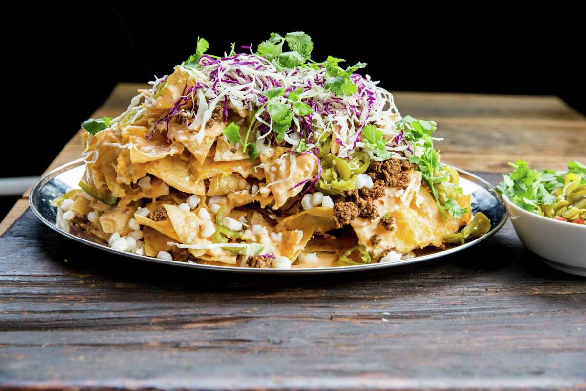 Silver Platter Nachos (tortilla chips with taco meat, pickled jalapeno and hominy, cabbage, melted cheese with pico and sour cream on the side) are among the new bar snacks at the Hay Merchant, Houston.