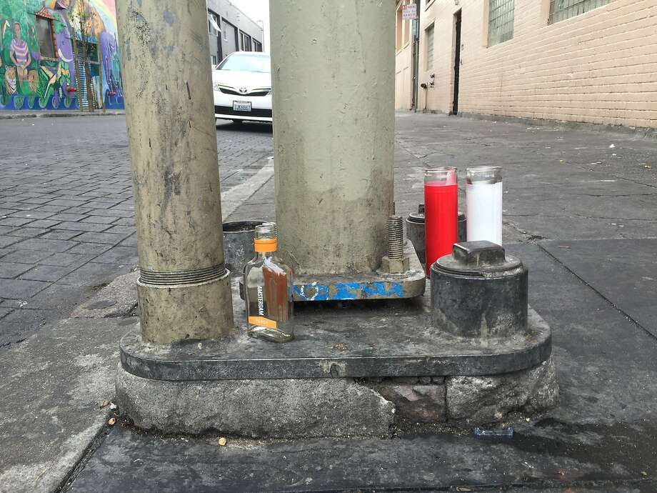 Candles and a bottle of booze mark the site at the corner of Sixth and Minna streets in San Francisco's South of Market neighborhood where a man was shot and killed late Monday night. Photo: Kevin Schultz, The Chronicle