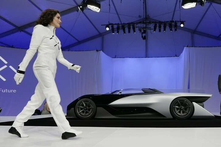 A driver walks in front of the FFZero1 by Faraday Future at CES Unveiled, a media preview event for CES International  Monday, Jan. 4, 2016, in Las Vegas. The high-performance electric concept car was unveiled during a news conference by Faraday Future. (AP Photo/Gregory Bull)