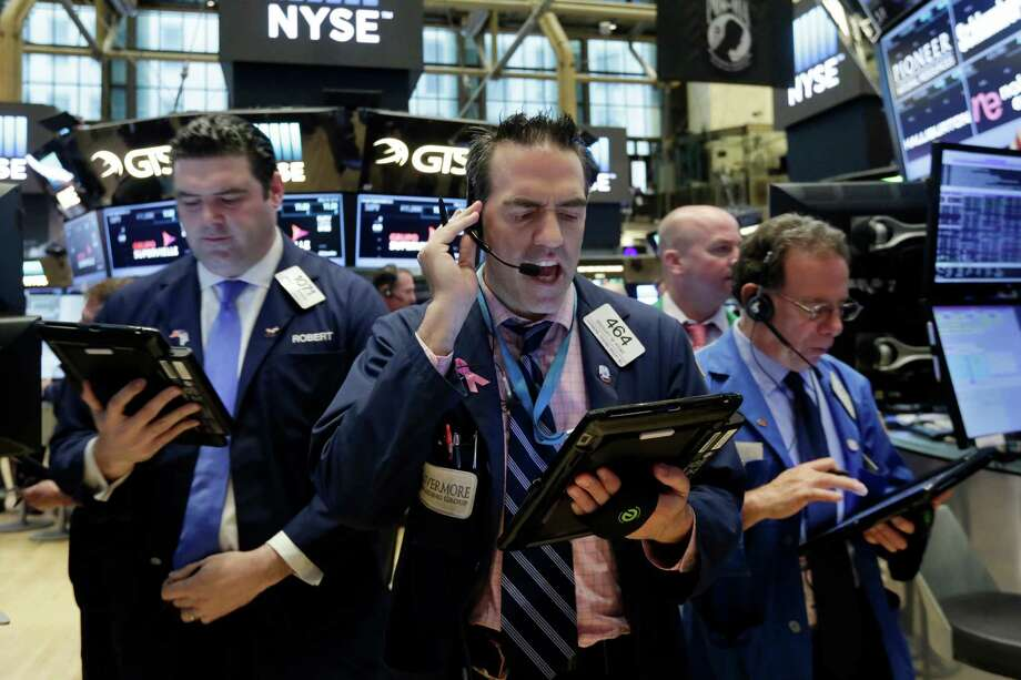 Trader Gregory Rowe, center, works on the floor of the New York Stock Exchange, Tuesday, May 24, 2016. Stocks are opening solidly higher on Wall Street, led by gains in technology stocks and banks. (AP Photo/Richard Drew) Photo: Richard Drew, STF / Copyright 2016 The Associated Press. All rights reserved. This material may not be published, broadcast, rewritten or redistribu
