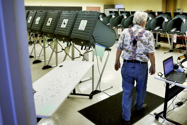 Election Clerk Chuck Hall walks through the voting room during the Democrat and Republican primary runoff elections at the Metropolitan Multi-Services Center Tuesday, May 24, 2016 in Houston.