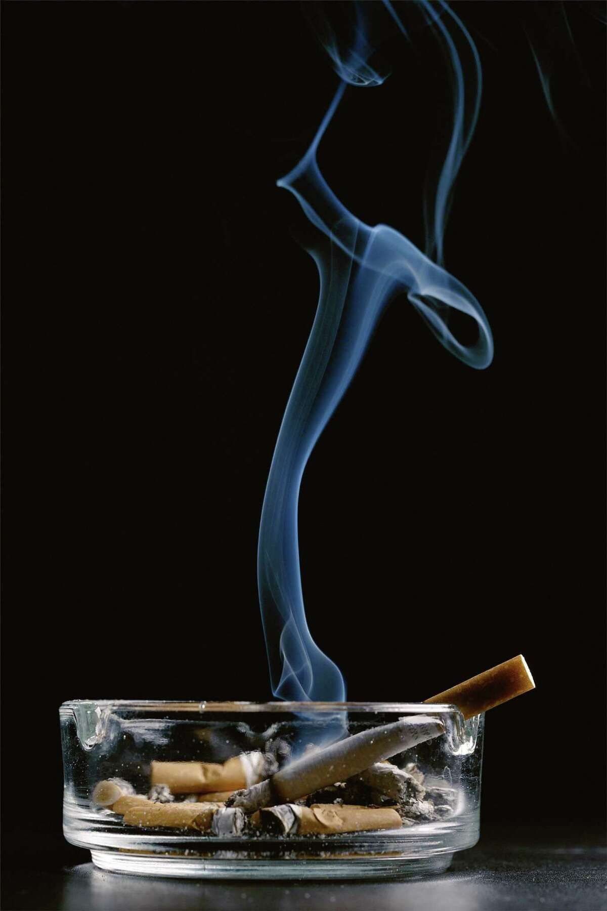 photoalto_6461554.jpg. Ashtray with cigarette butts and lit cigarette smoking against black background. ROYALTY-FREE IMAGE can be used online and reused. Credit: PhotoAlto / WireImage