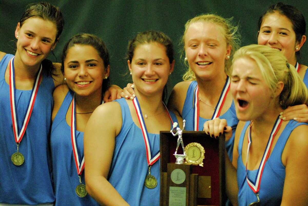 The Darien girls tennis team celebrates winning the FCIAC championship after beating Staples 5-2 on Tuesday.
