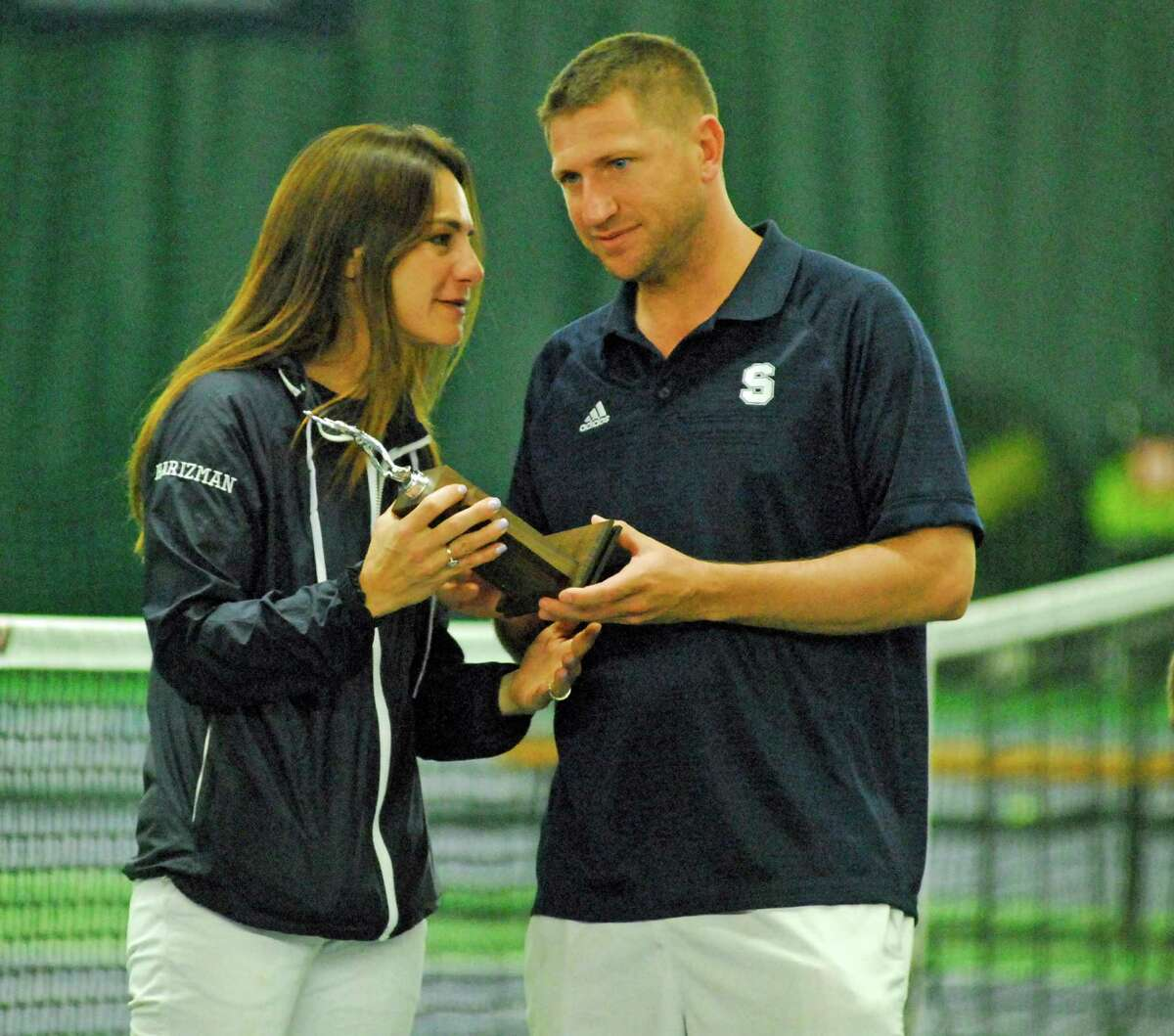 Staples coach Paco Fabian, right, and assistant coach Kim Harizman hold a trophy after finishing runners-up to Darien in the FCIAC girls tennis final on Tuesday.