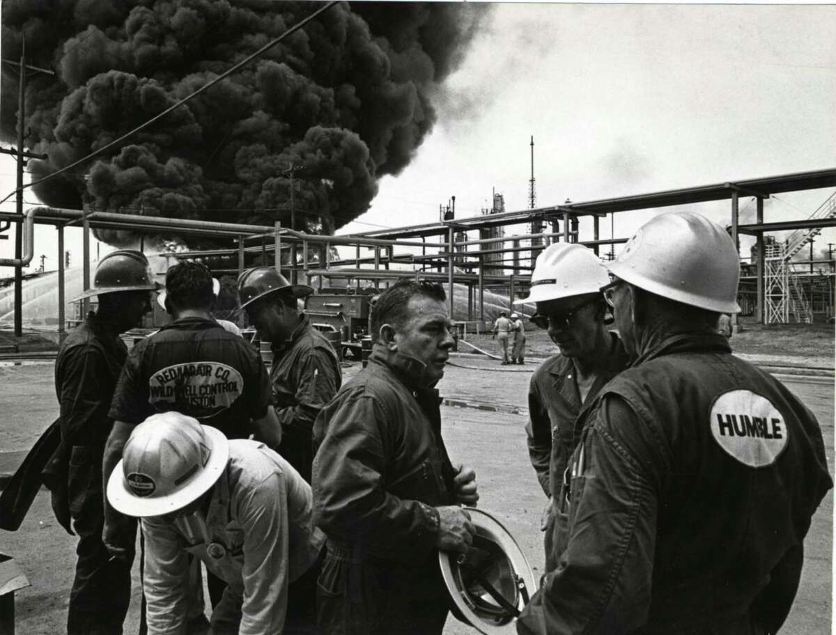 """Red Adair, center, talks with workers from his """"Red Adair Wild Well Control"""" team at a 1965 fire in Baytown."""