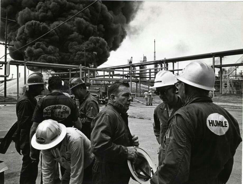 "Red Adair, center, talks with workers from his ""Red Adair Wild Well Control"" team at a 1965 fire in Baytown. Photo: David Nance, Staff / Houston Chronicle"