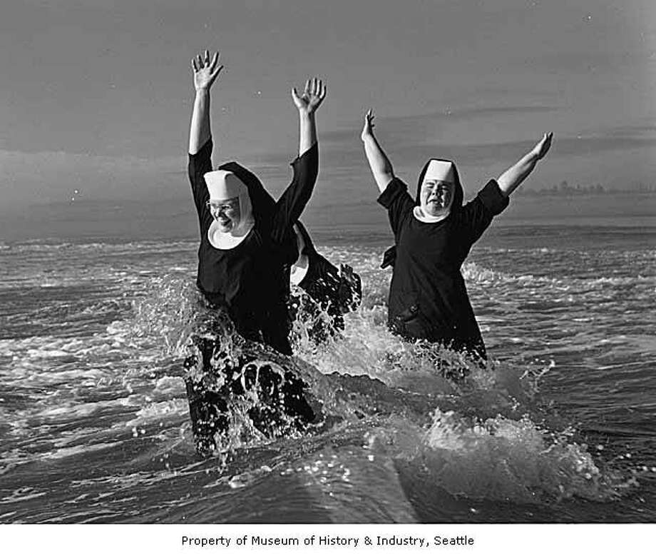 """A group of nuns from the Order of Saint Benedict enjoyed their summer vacation at the beach in Grayland. Here Sisters Ruth (left) and Agnes play in the surf; partly hidden is Sister Rita. After a weeklong break they returned ""refreshed and strengthened"" to their routine duties of teaching school in the Seattle and Tacoma area."" -MOHAI. Photo, dated Aug. 21, 1960, courtesy MOHAI, Seattle P-I Collection, image number 1986.5.6047. Photo: Courtesy MOHAI"