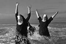 """""""A group of nuns from the Order of Saint Benedict enjoyed their summer vacation at the beach in Grayland. Here Sisters Ruth (left) and Agnes play in the surf; partly hidden is Sister Rita. After a weeklong break they returned """"refreshed and strengthened"""" to their routine duties of teaching school in the Seattle and Tacoma area."""" -MOHAI. Photo, dated Aug. 21, 1960, courtesy MOHAI, Seattle P-I Collection, image number 1986.5.6047."""