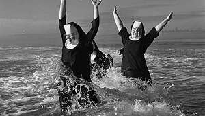 """A group of nuns from the Order of Saint Benedict enjoyed their summer vacation at the beach in Grayland. Here Sisters Ruth (left) and Agnes play in the surf; partly hidden is Sister Rita. After a weeklong break they returned ""refreshed and strengthened"" to their routine duties of teaching school in the Seattle and Tacoma area."" -MOHAI. Photo, dated Aug. 21, 1960, courtesy MOHAI, Seattle P-I Collection, image number 1986.5.6047."