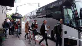 A shuttle bus bound for Silicon Valley more than 40 miles away picks up riders in the heart of San Francisco's Mission neighborhood. The buses cater to employees of Apple, Google, Facebook and others. Gentrification squeezed many less-affluent San Franciscans out of cherished neighborhoods.
