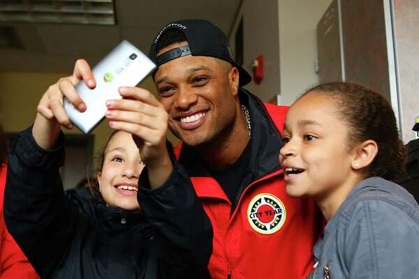 Gia Culbertson, 9, left, and Lynneah Childs, 10, take a selfie with Seattle Mariner Robinson Can— at Concord International School, Tuesday, May 24, 2016.  Can— visited with students and the City Year team he sponsors at Concord as they work with bi-lingual students as peer mentors.