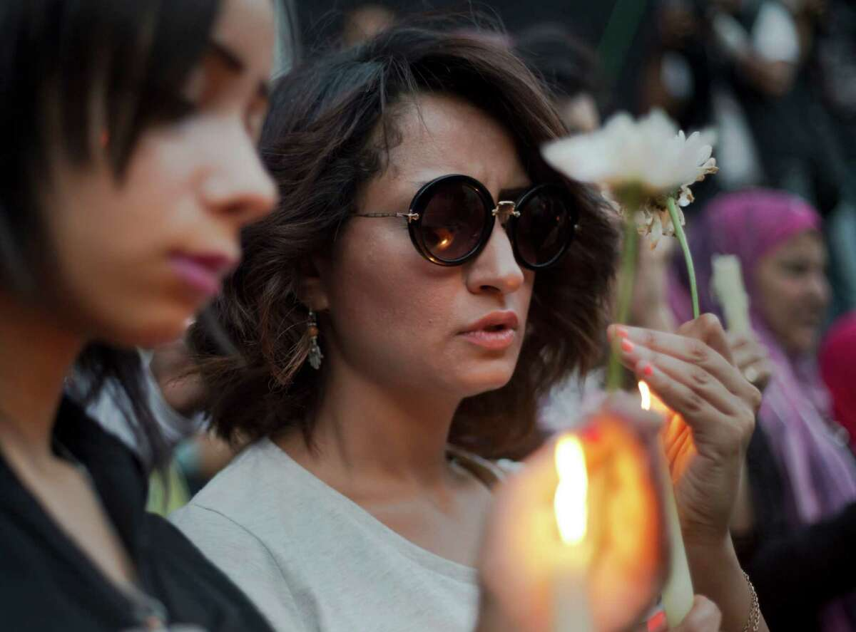 An Egyptian journalist holds a candle during a candlelight vigil for the victims of EgyptAir flight 804 in front of the Journalists' Syndicate in Cairo, Egypt, Tuesday, May 24, 2016. The cause of Thursday's crash of the EgyptAir jet flying from Paris to Cairo that killed all 66 people aboard still has not been determined. Ships and planes from Egypt, Greece, France, the United States and other nations are searching the Mediterranean Sea north of the Egyptian port of Alexandria for the jet's voice and flight data recorders.