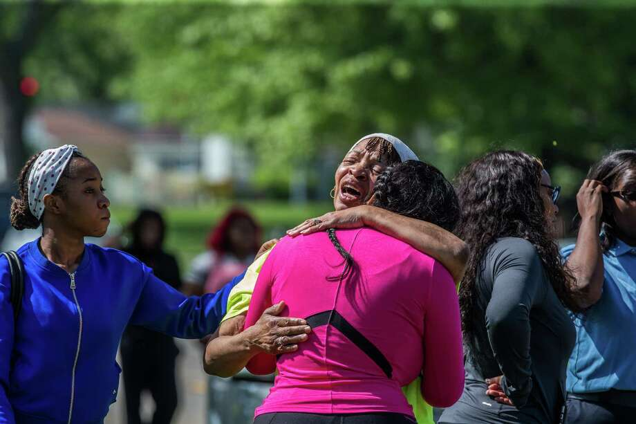 Friends and family console each other as the FBI investigates a shootingoutside Chicago that left two agents wounded and a suspect dead. Photo: Zbigniew Bzdak, MBR / Chicago Tribune