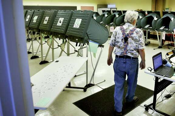 Election clerk Chuck Hall monitors the voting room during primary runoff elections at the Metropolitan Multi-Services Center.