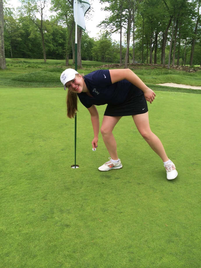 Wilton's Nora Noel Nolan goes to pick up her ball after acing the 7th hole at the New Canaan Country Club in the Warriors' match against New Canaan. Photo: Contributed / Contributed Photo / Contributed photo