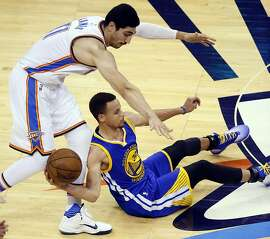 Golden State Warriors guard Stephen Curry (30) tries to pass a loose ball as Oklahoma City Thunder center Enes Kanter (11) defends in Game 4 of the NBA basketball Western Conference finals in Oklahoma City, Tuesday, May 24, 2016. (AP Photo/Sue Ogrocki)