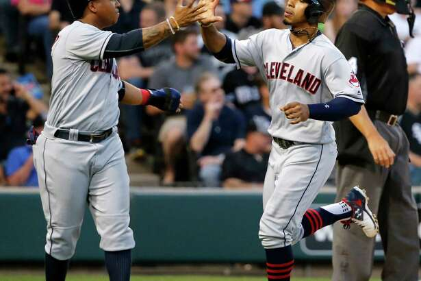 Cleveland Indians' Jose Ramirez, left, and Francisco Lindor celebrate after they scored on Mike Napoli's triple off Chicago White Sox starting pitcher Chris Sale during the third inning of a baseball game Tuesday, May 24, 2016, in Chicago. (AP Photo/Charles Rex Arbogast) ORG XMIT: CXS118