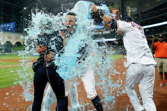 Houston Astros shortstop Carlos Correa (1) gets doused by Powerade after his RBI single wins the game during the thirteenth inning of an MLB baseball game at Minute Maid Park, Tuesday, May 24, 2016.